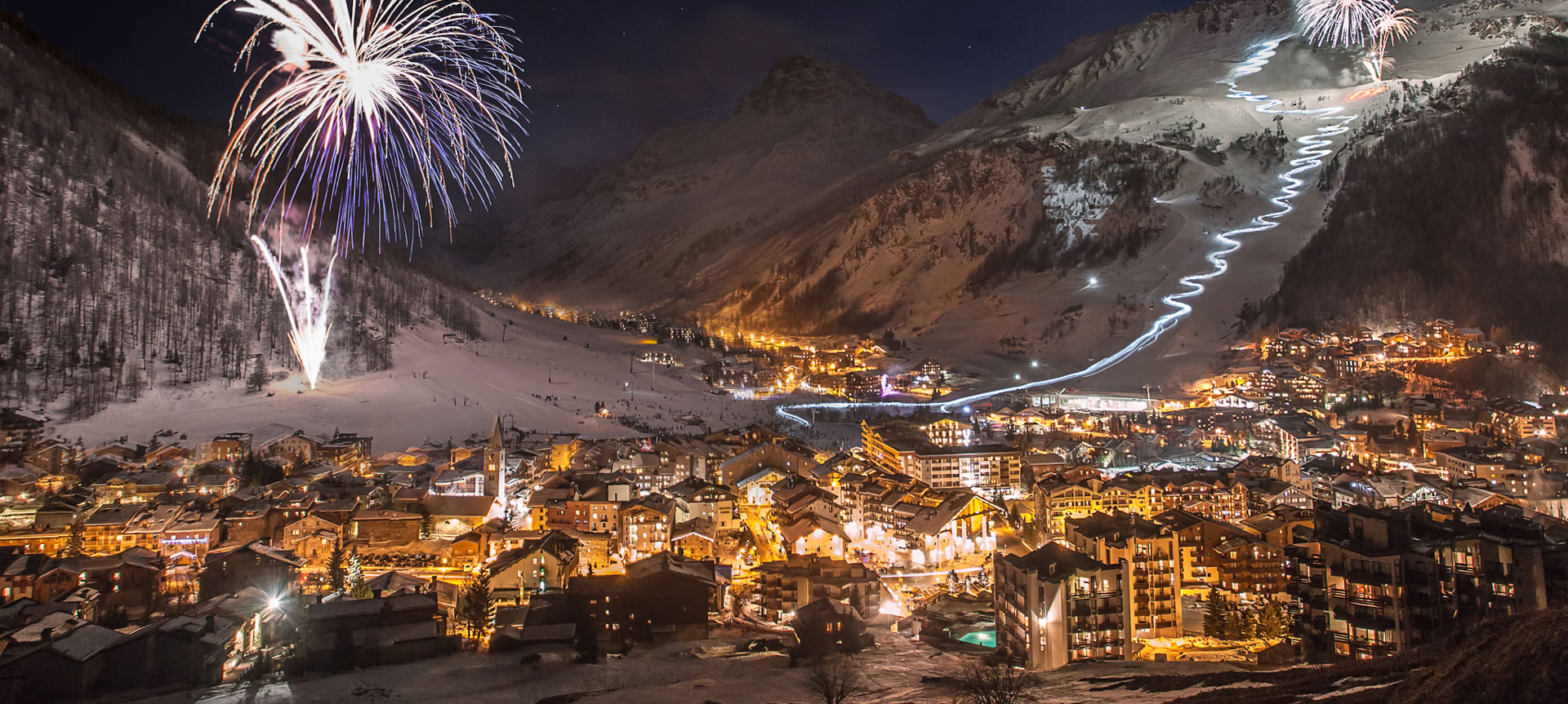 The village of Val d'Isere seen at night light up by fireworks on the nursery slopes and 300 ski instructors doing a torchlight descent of the Face de Bellevarde