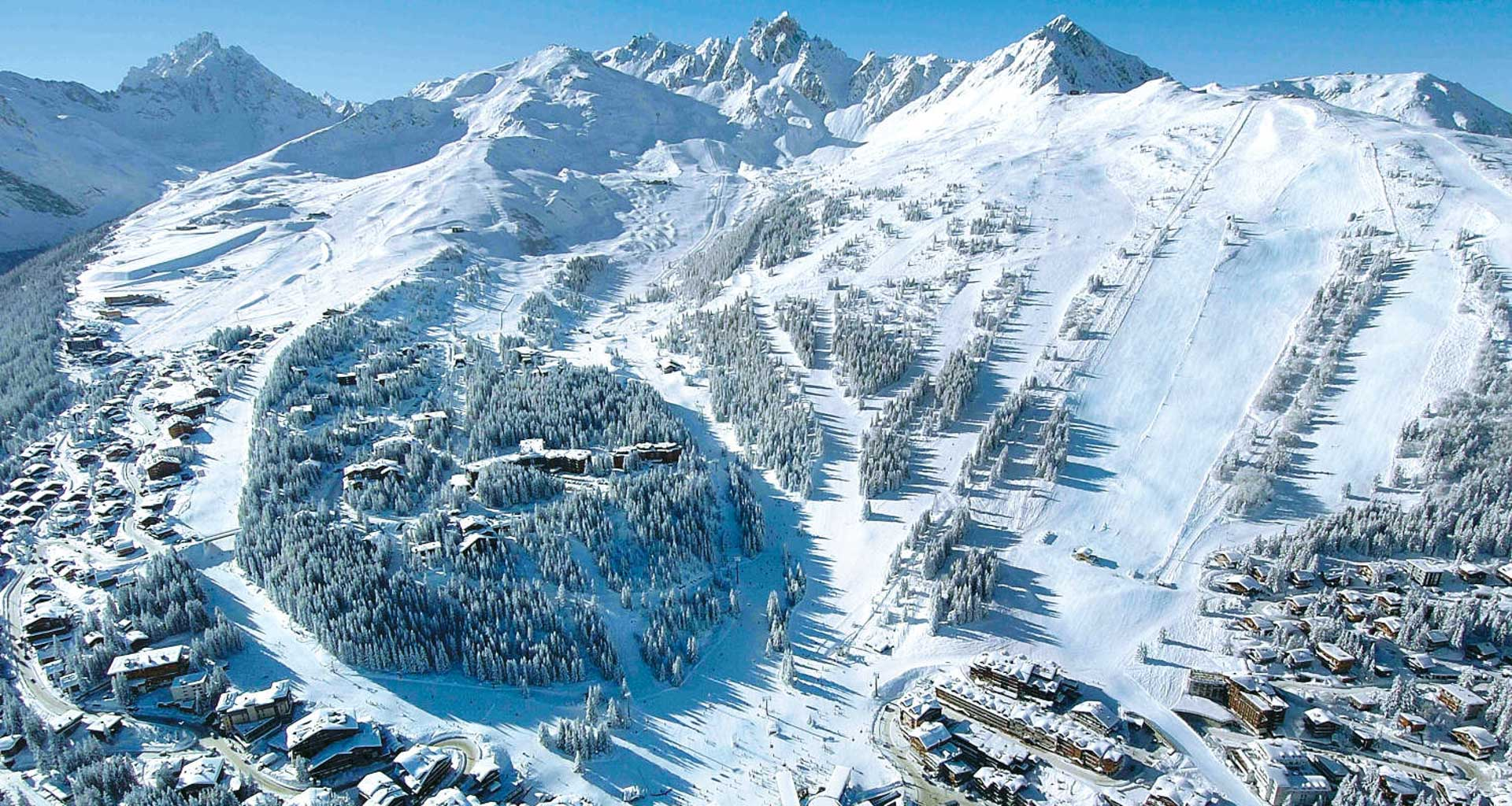 The village of Courchevel sits on the snowfront and in the trees underneath the beautifully groomed runs of the mountains above.