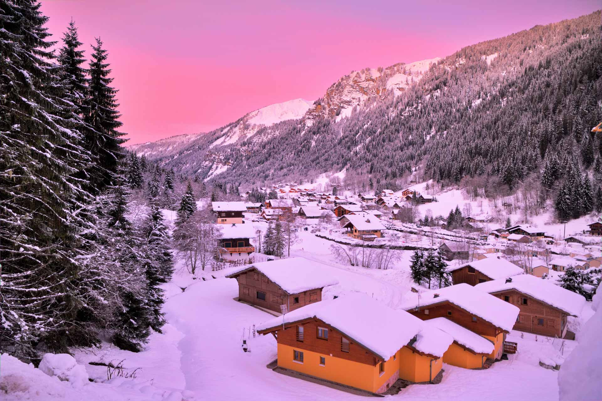 A beautiful pink and purple sunset washes over the mountains and chalets of the Chatel ski area