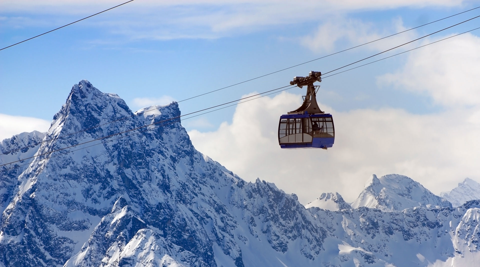 A blue cable car rises up in front of formidable mountain peaks in St Anton am Arlberg