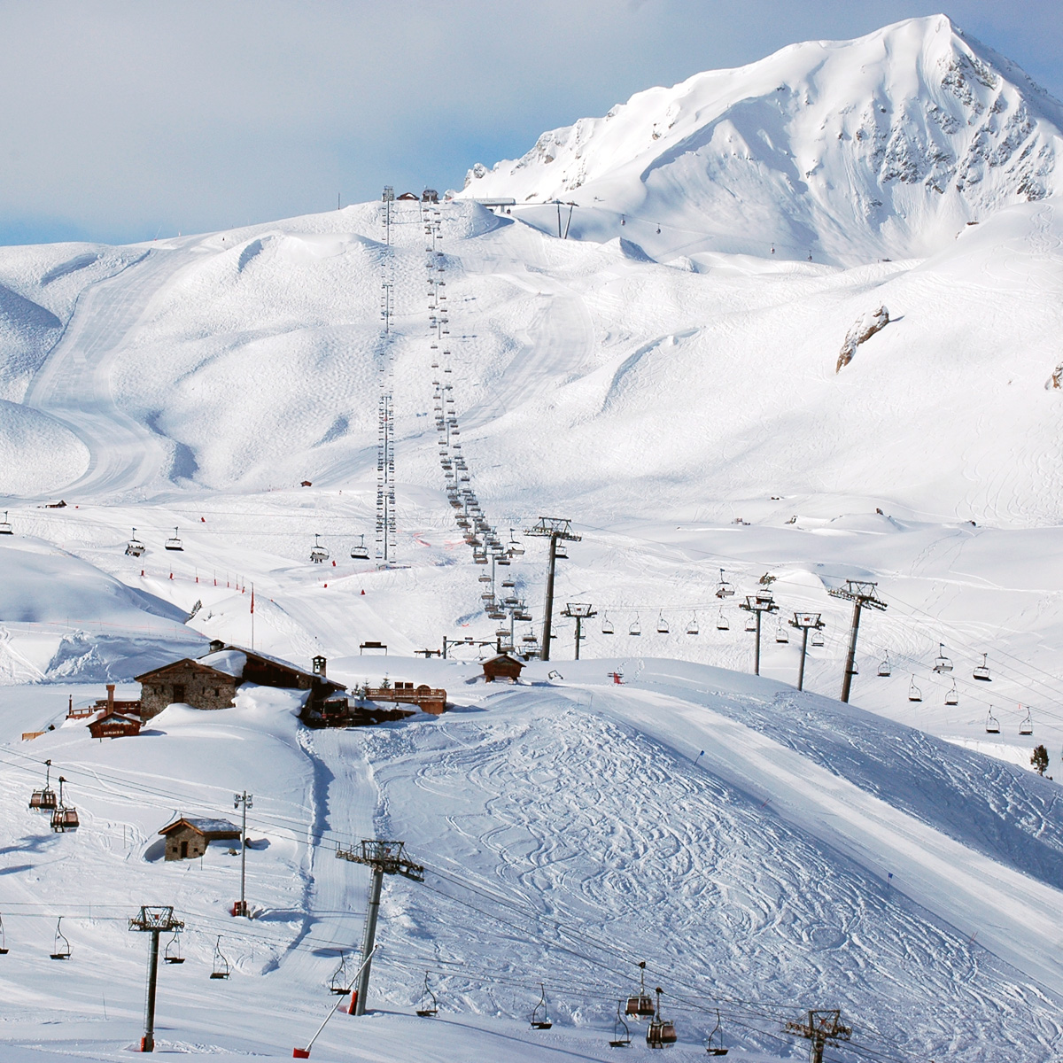 Two ski lifts reach far in to the distance taking skiers up the majestic, snowy, Aiguille rouge