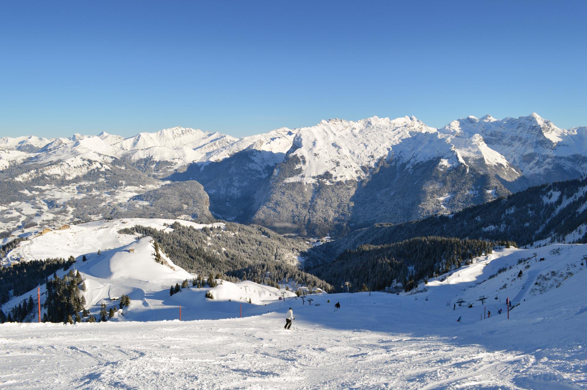 A skier in white going down the slope in the ski resort of Samoens