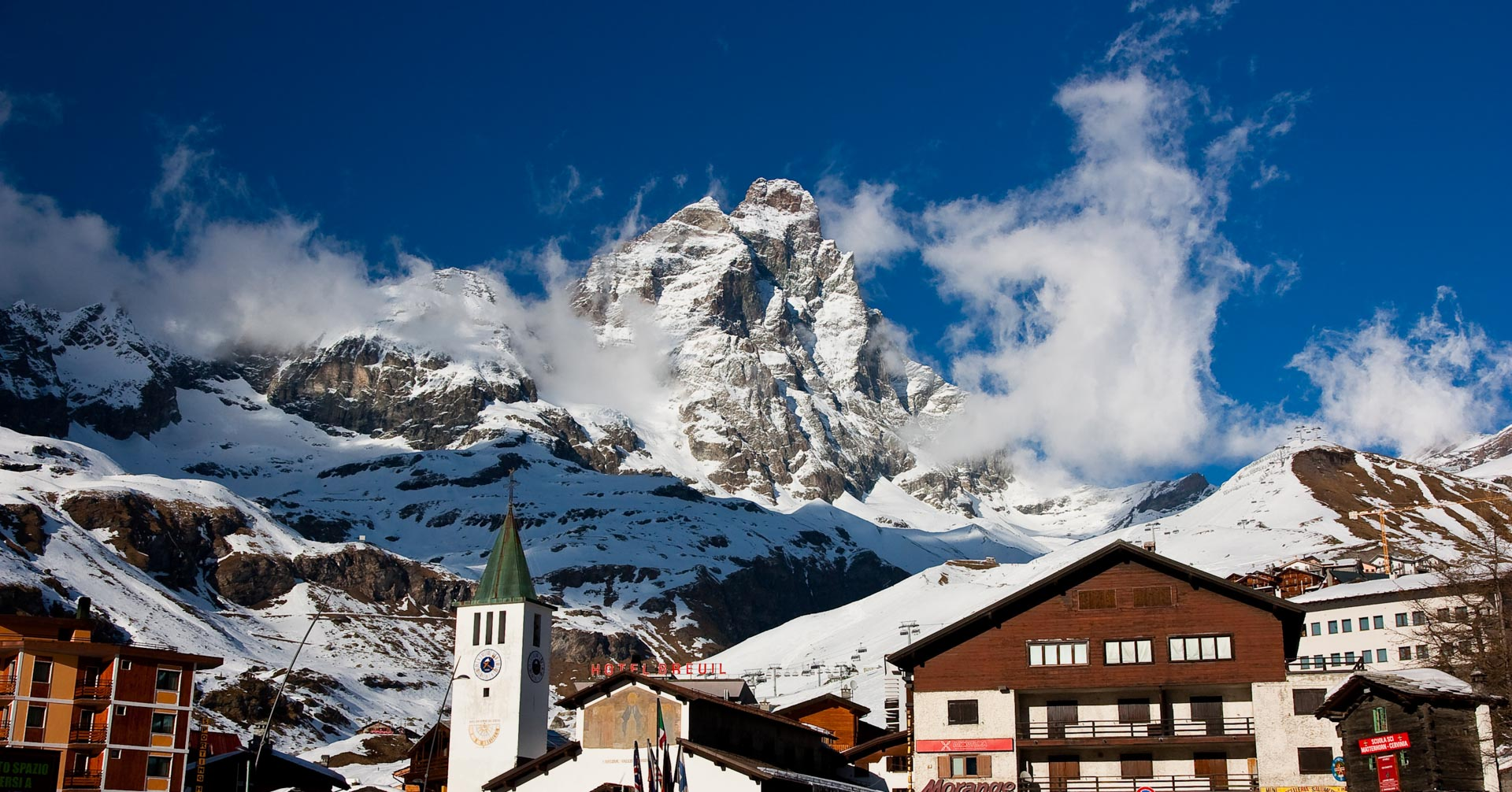 Mountains dominate the skyline of the picturesque, snow-covered Italian village of Cervinia