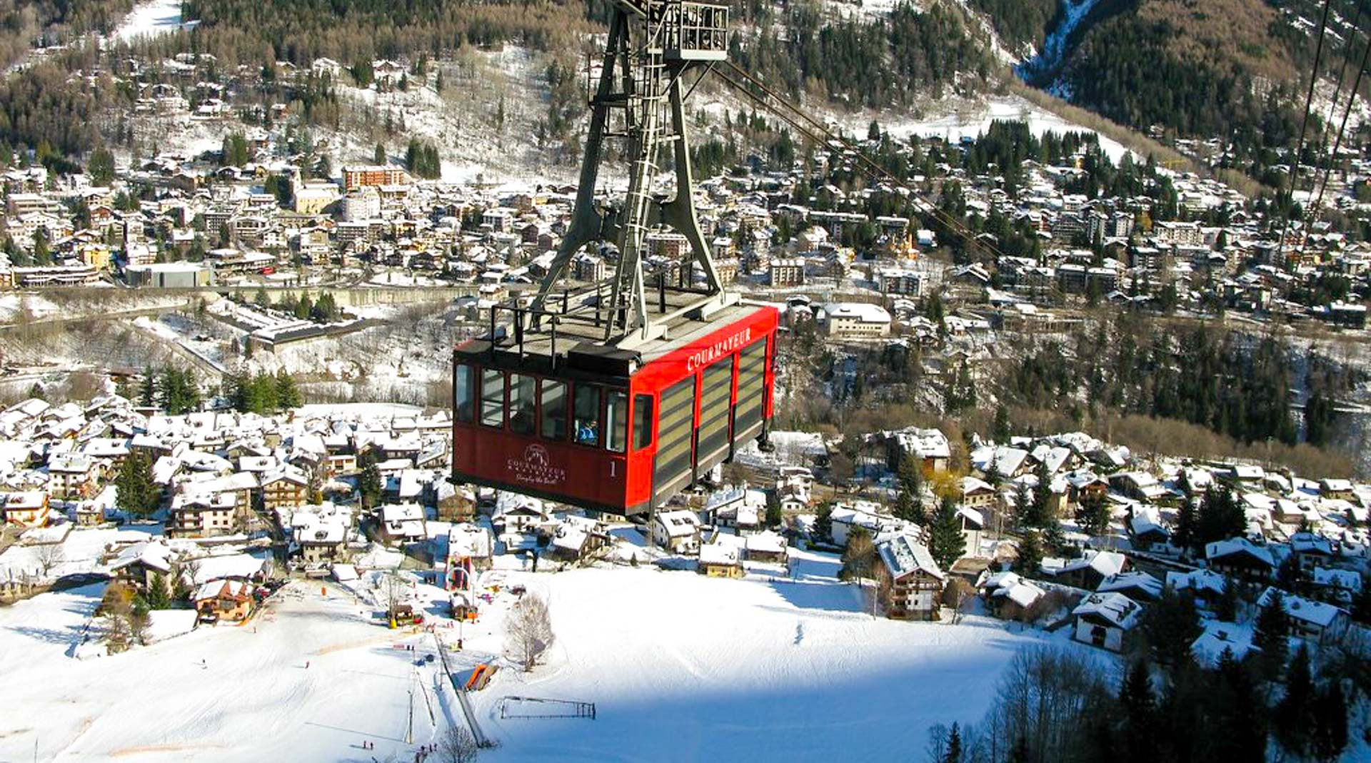 The giant red cable car rises up from the ski resort of Courmayeur, carrying skiers to the ski slopes above