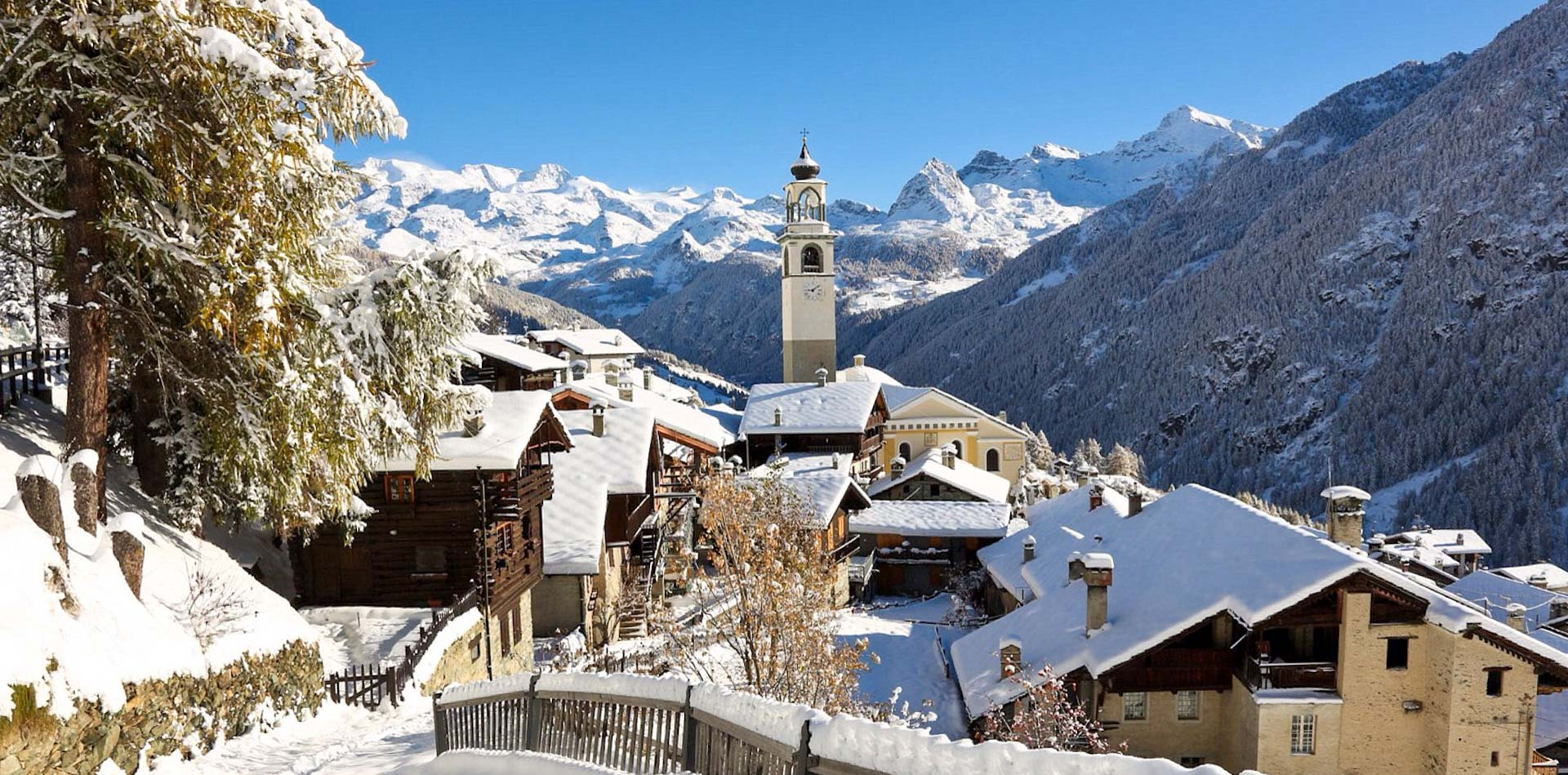 A beautiful snow covered church steeple stands above the snow covered chalets of Champoluc, which sits in front of mountains