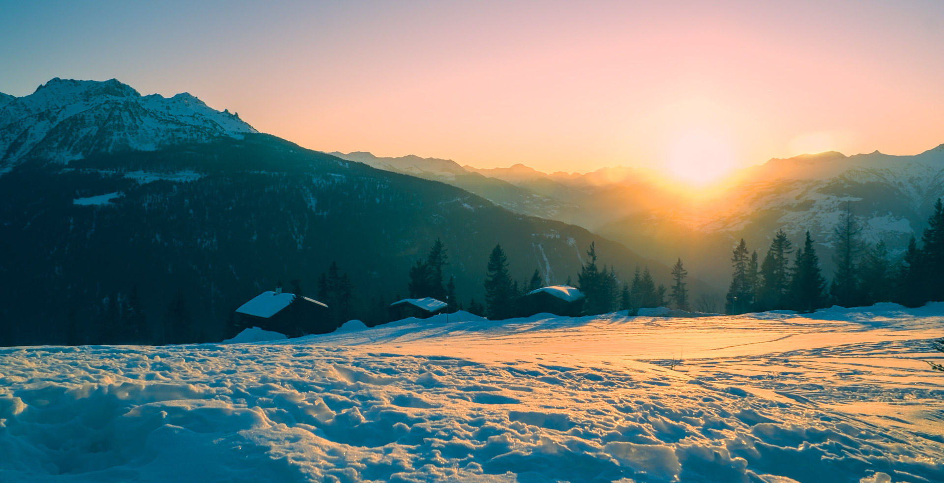 The sun setting over the mountains and snowfields of La Rosiere, tinting the sky pink and the ground yellow