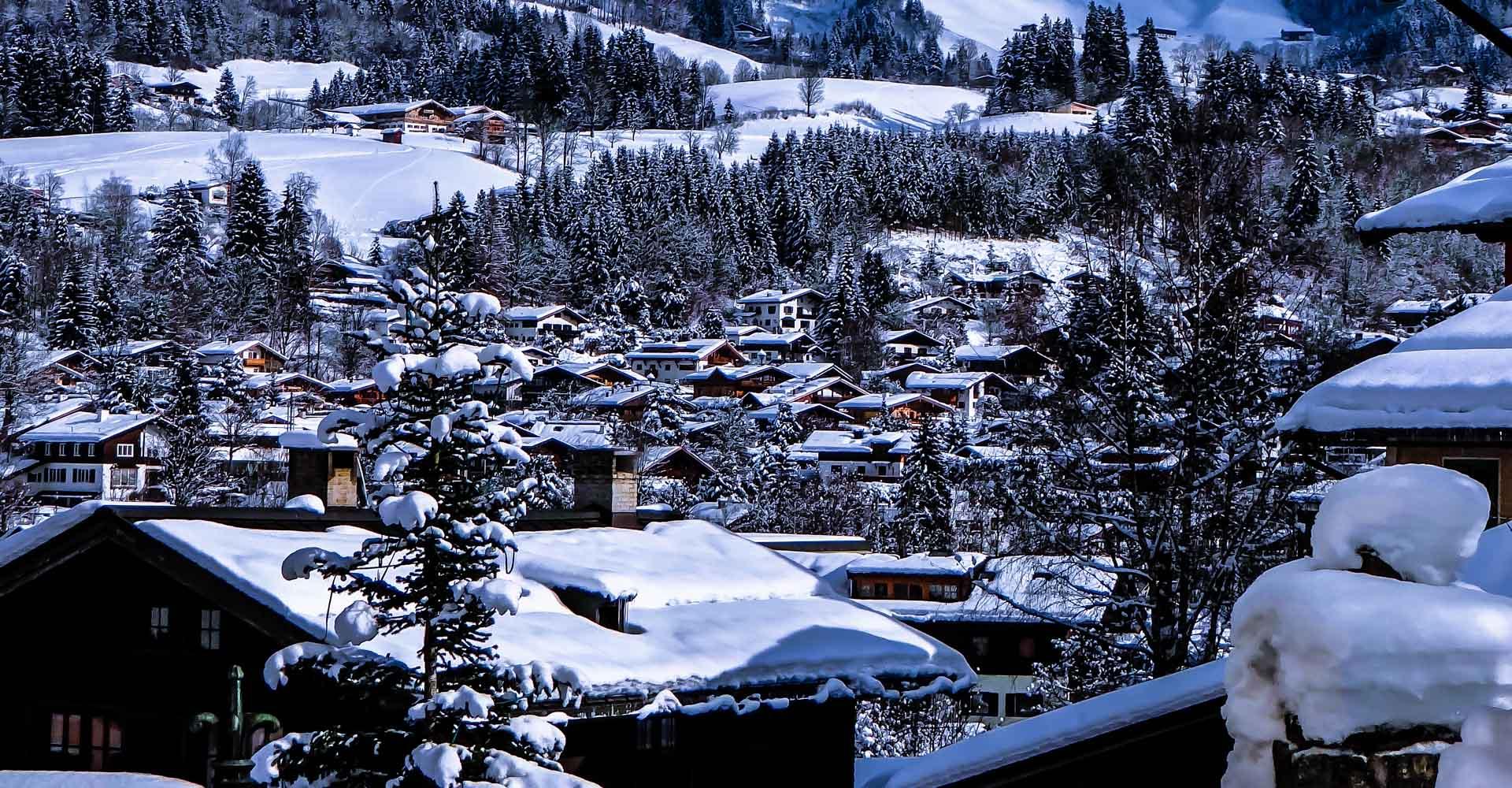 Blauer Himmel und Wolken über dem schneebedeckten Dorf und den Bergen von Kitzbühel
