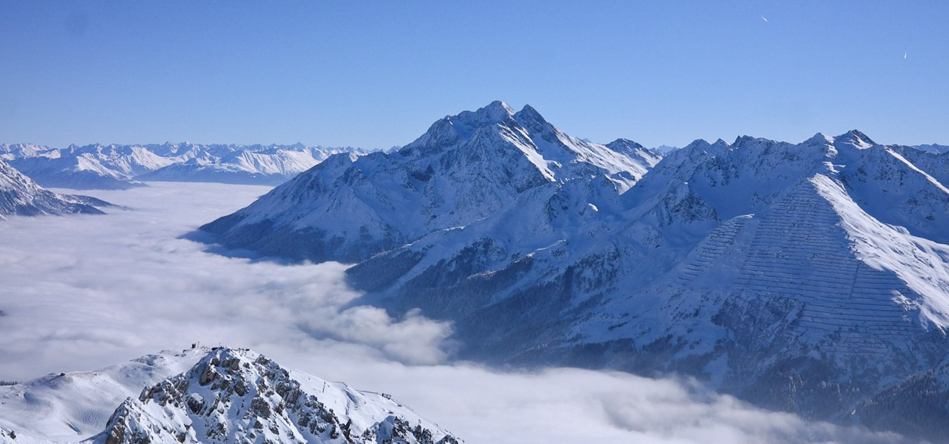 The highest peaks in the ski resort of Zurs reaching up above a sea of clouds