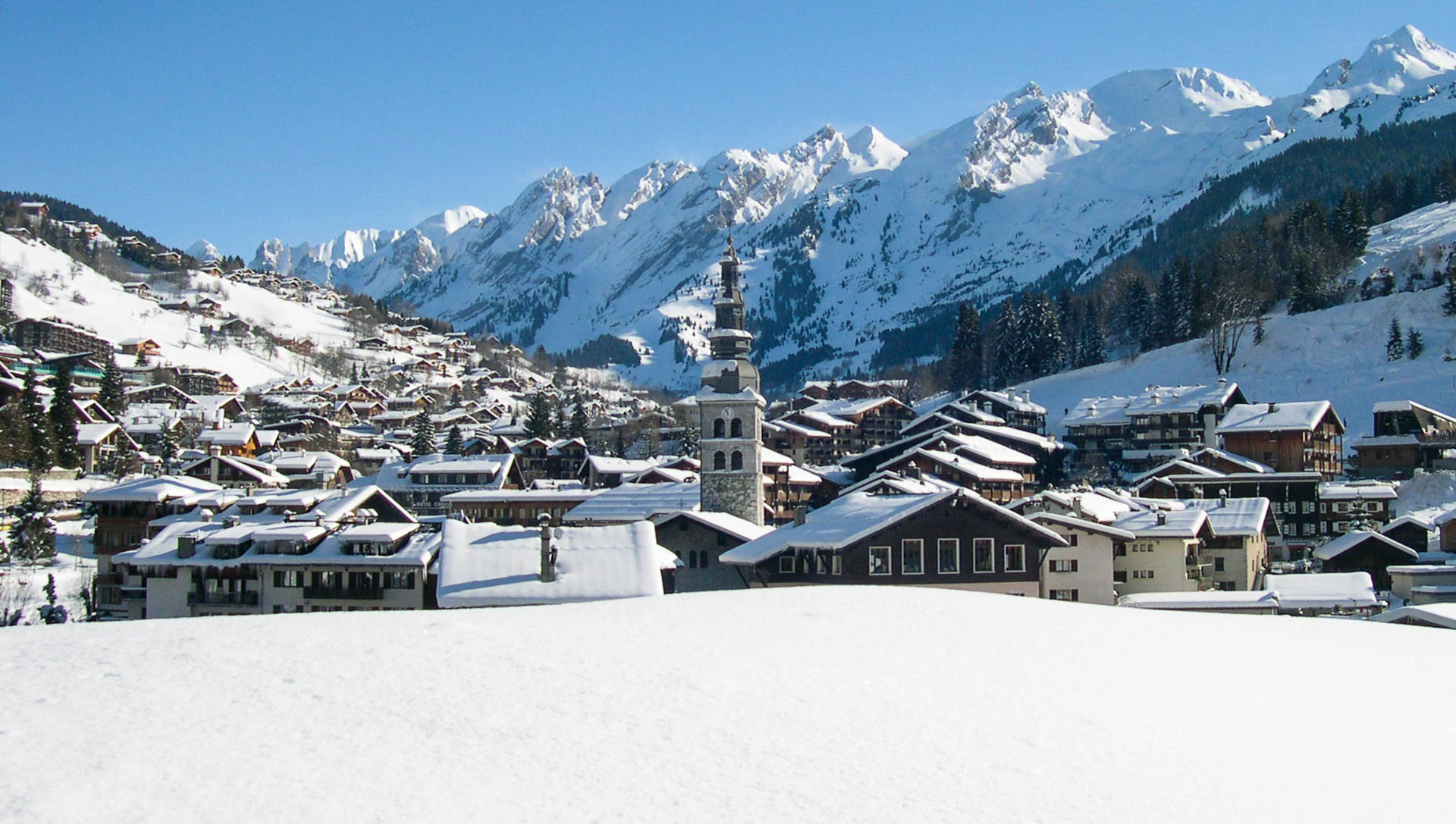 A proud church spire juts up amongst snow-covered roofs in the ski resort of La Clusaz