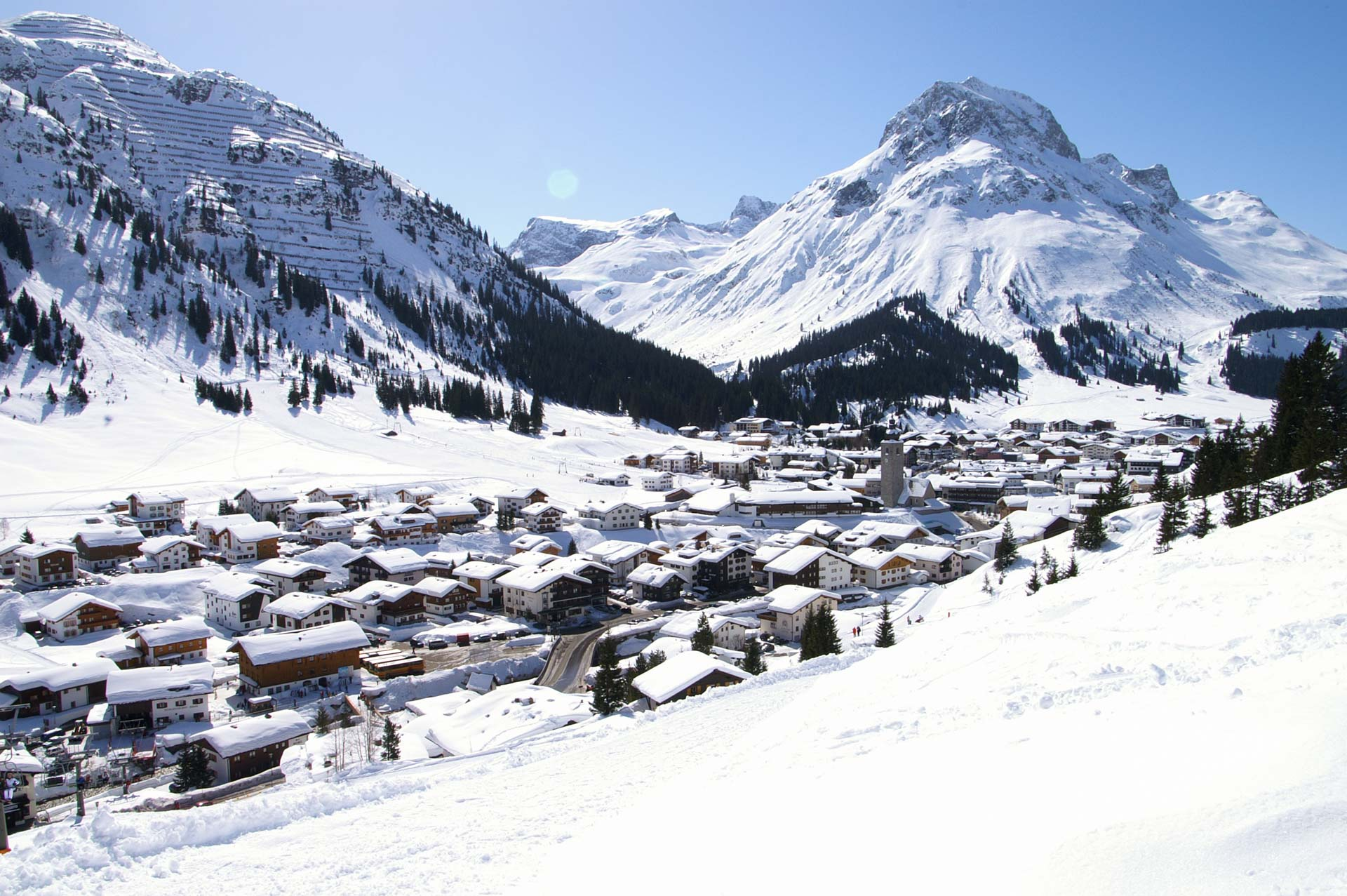 Two dramatic snow covered mountains rise up behind the beautiful Alpine ski resort of Lech am Arlberg