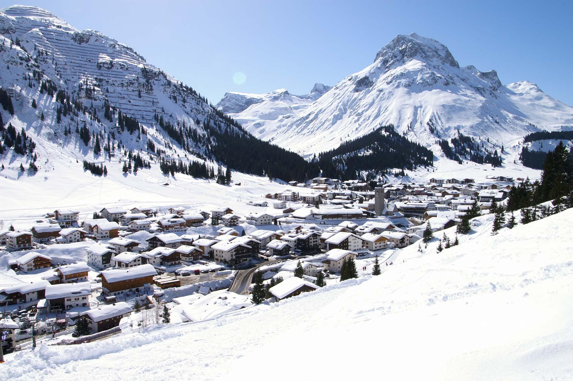 Blauer Himmel und Wolken über dem schneebedeckten Dorf und den Bergen von Lech am Arlberg