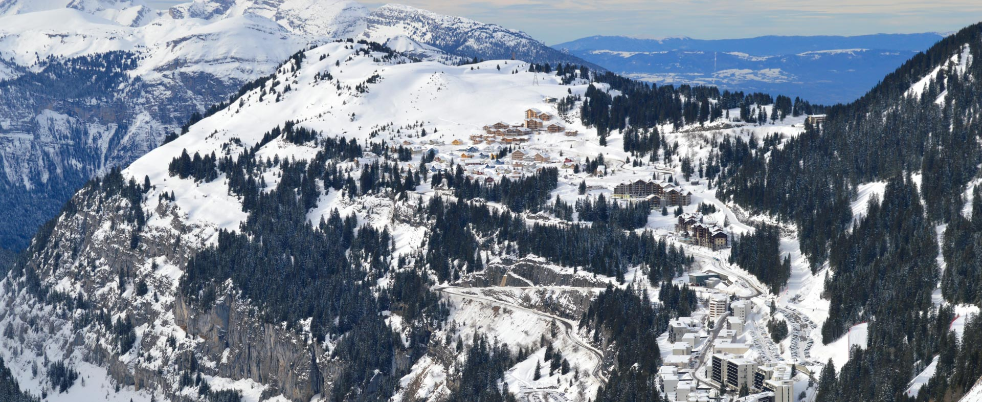 The village of Flaine sits nestled in the mountain side, above evergreen trees and below the ski slopes
