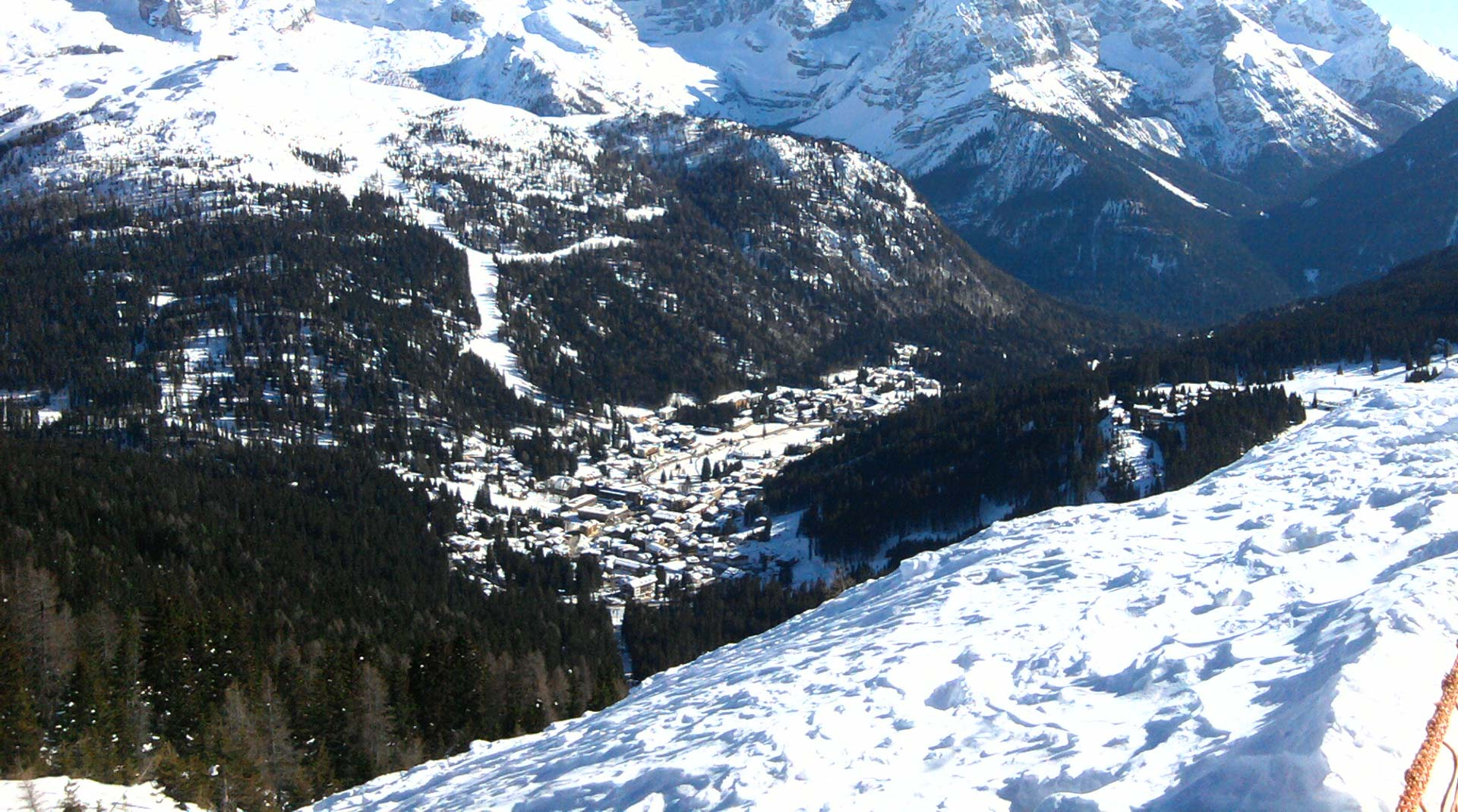 The ski resort of Madonna di Campiglio seen nestled in a valley of trees from the ski slopes above