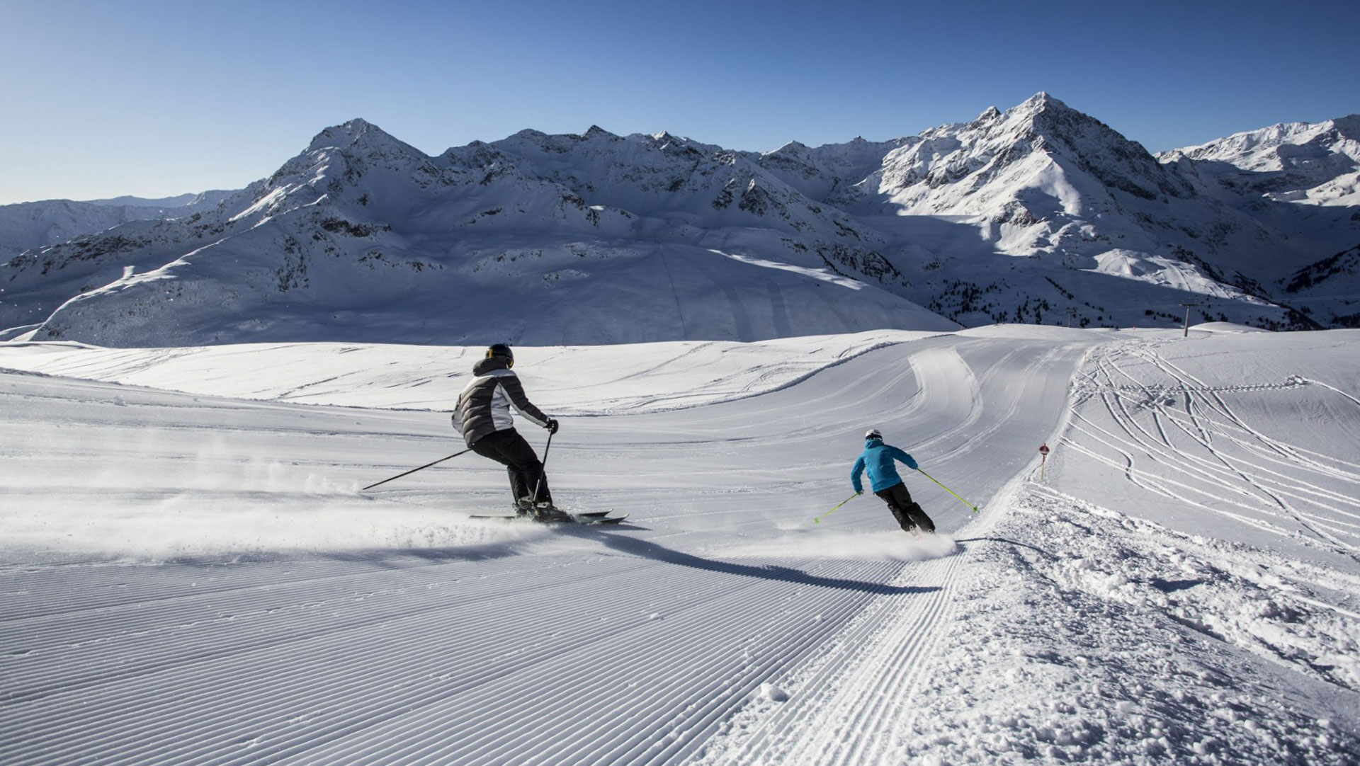 Two skiers carve down freshly groomed corduroy pistes in Kuthai ski area