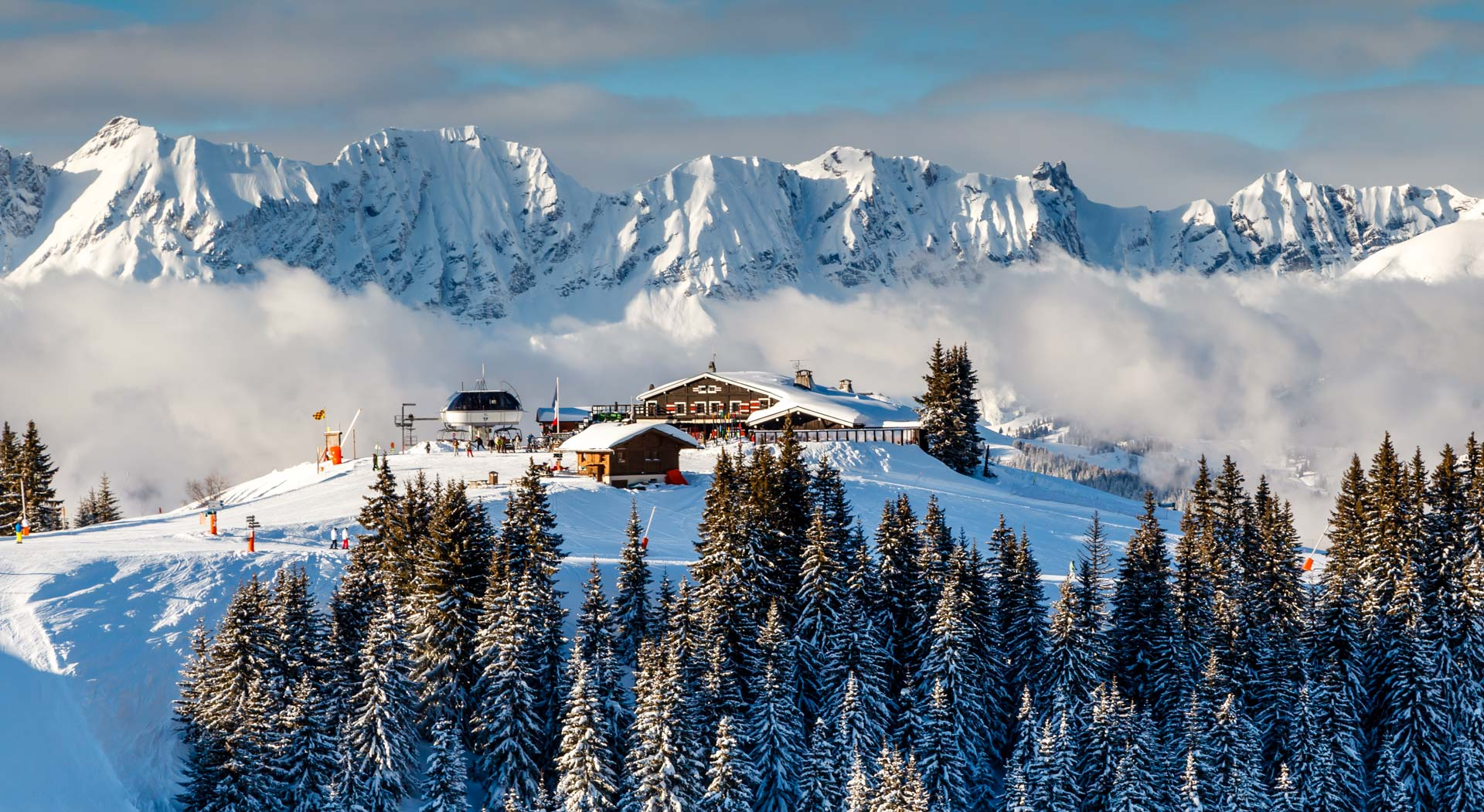 Perched atop a mountain, in front of a sea of clouds are a chair lift and a mountainside restaurant in Megeve