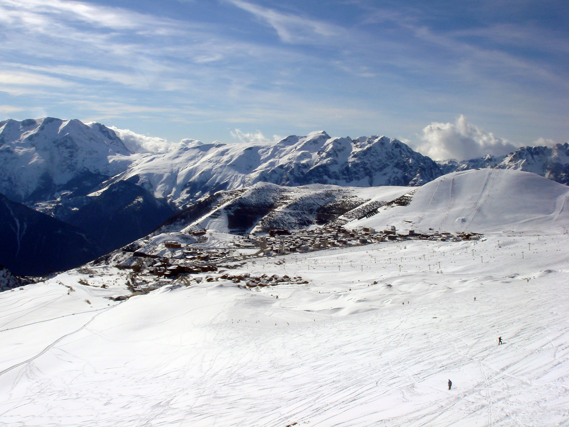 The ski resort Alpe d'Huez is a cluster of chalets and buildings nestled in large, snowy mountains underneath a blue sky