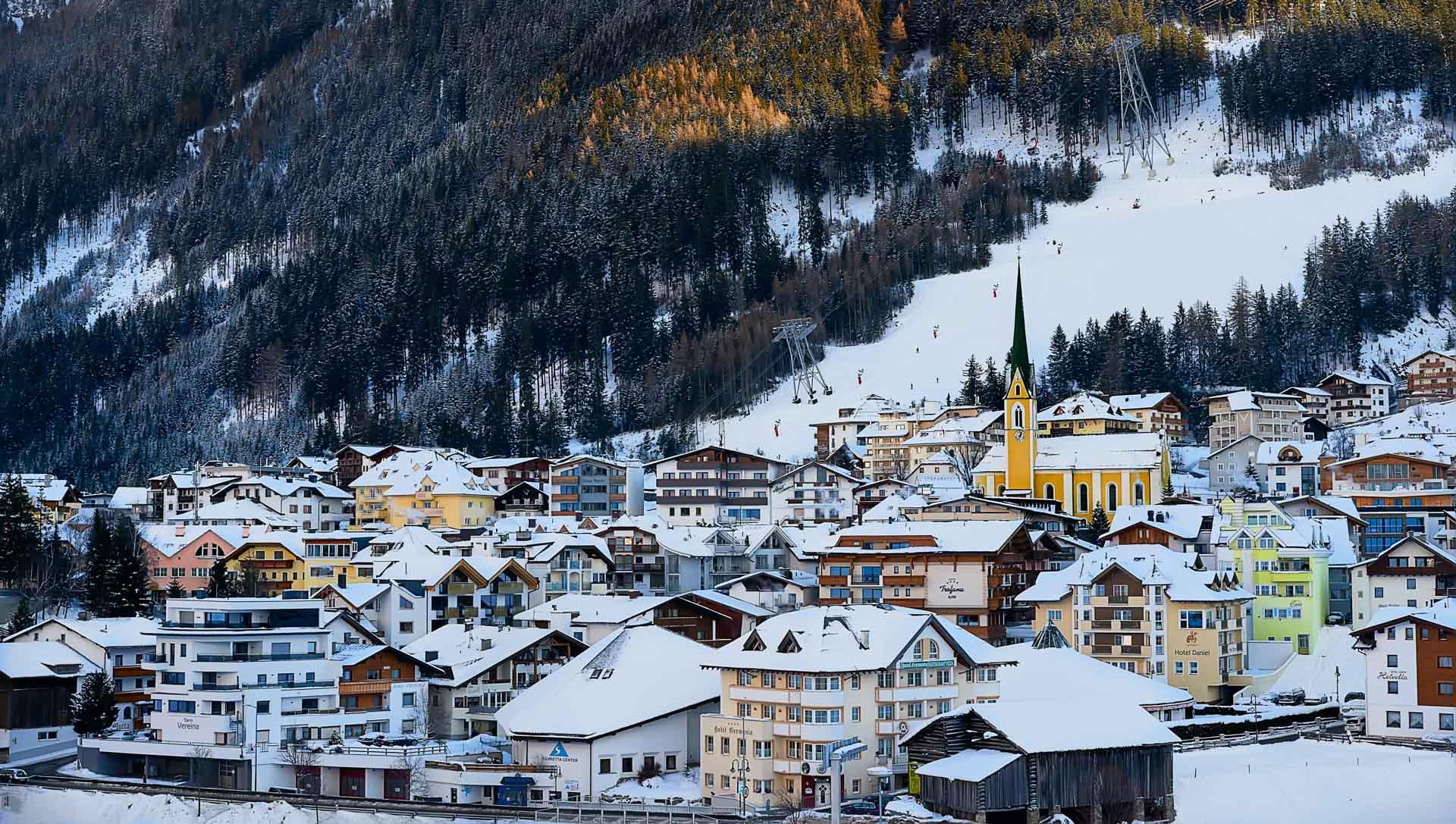 Blauer Himmel und Wolken über dem schneebedeckten Dorf und den Bergen von Ischgl