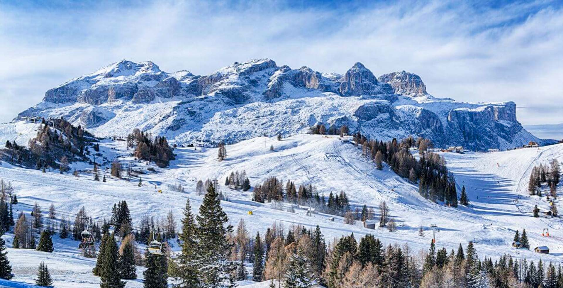 The peaks of the snow-covered Dolomite mountains rise up behind the ski slopes of La Villa ski resort
