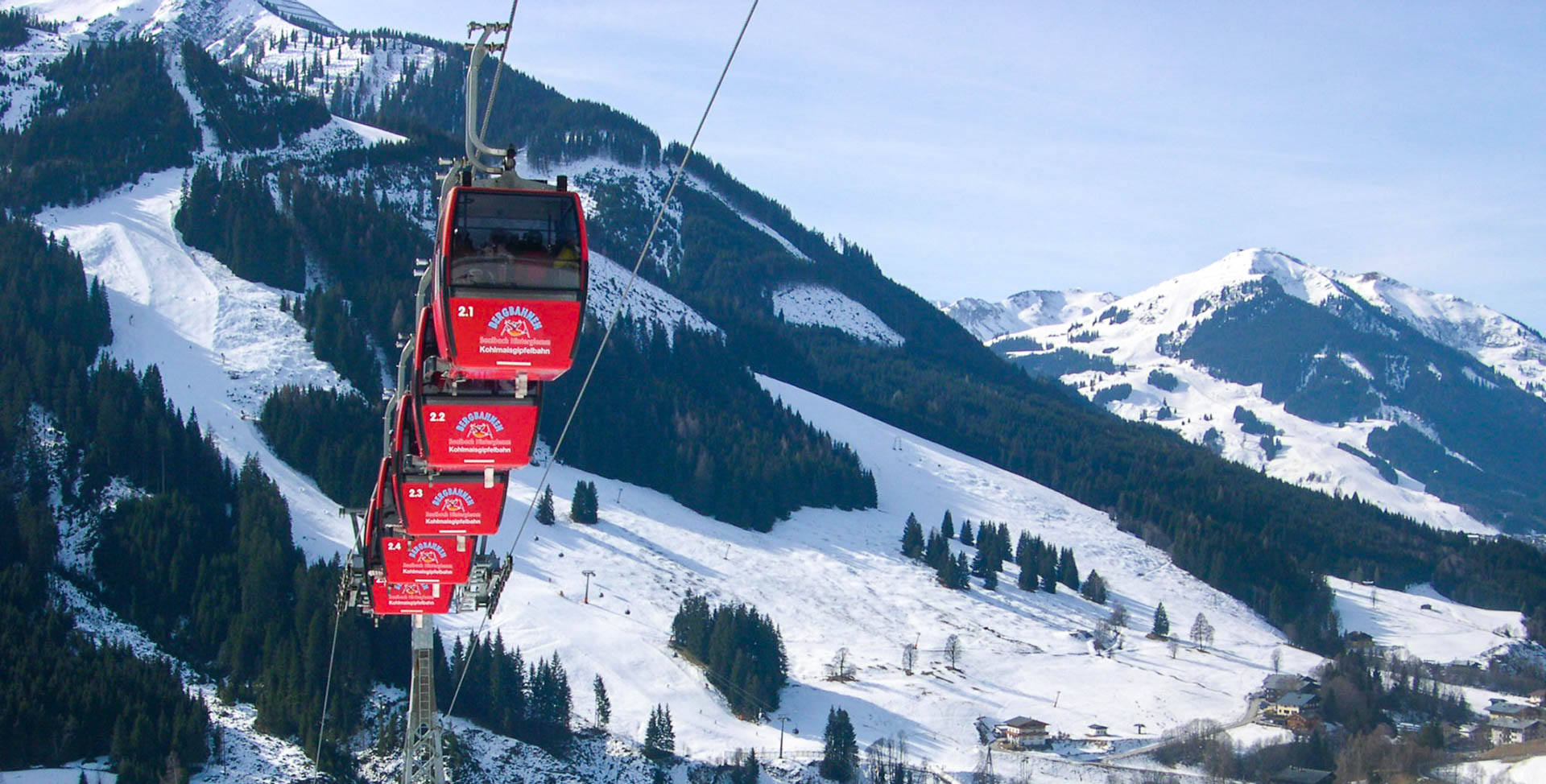 The bright red gondolas of the Kohlmais Group Lift rise above the slopes and towards the mountain peaks of Saalbach-Hinterglemm ski area
