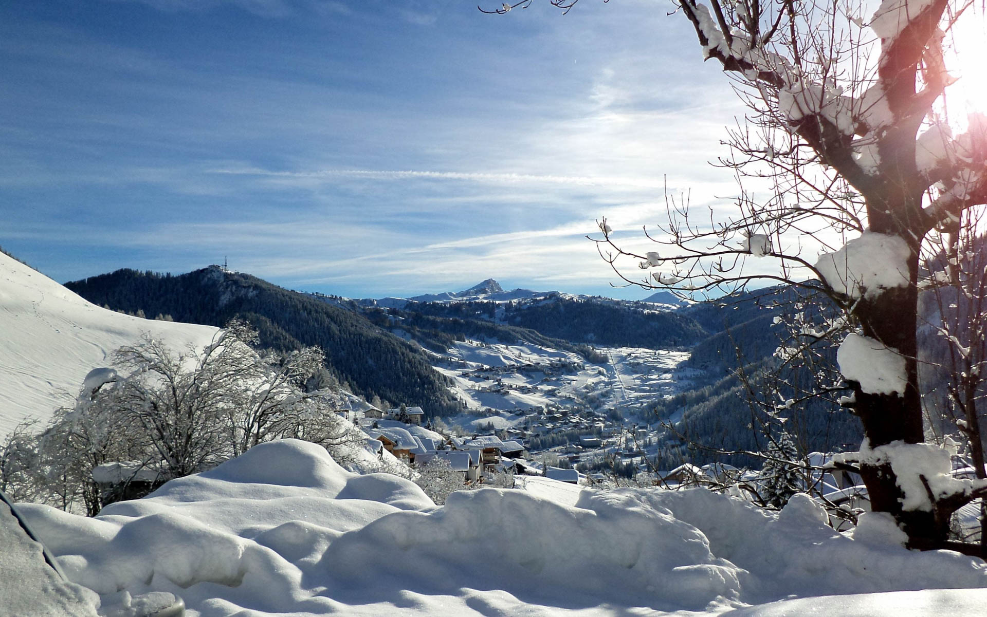 A view of the ski resort of Colfosco seen from a distance with the majestic mountains of the ski area behind it.